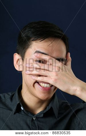 Smiling young Asian man looking at camera through his fingers