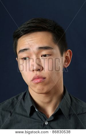 Romantic young Asian man looking down
