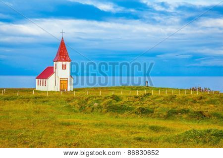 White Chapel. Chapel with red roof on the north shore of the fjord in Iceland