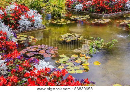 Delightful landscaped and floral park Butchart Gardens on Vancouver Island. Small pond, overgrown with flowers