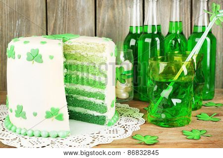 Still life with sliced cake and green beer for Saint Patrick's Day on wooden table and planks background