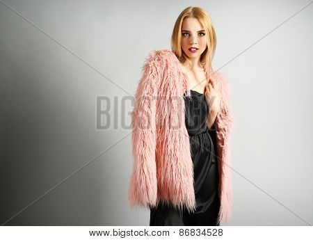 Expressive young model in pink fur coat and black dress on gray background