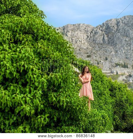 Woman standing in green plants on the mountains