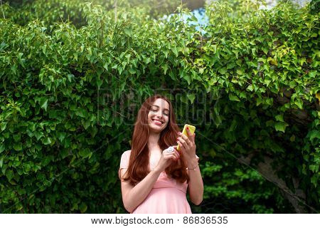 Woman using phone on green ivy background