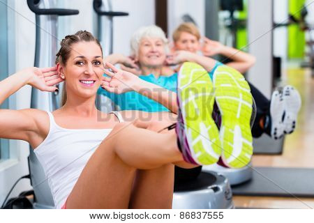 Group of senior and young people on vibrating plates in gym training abs for fitness sport