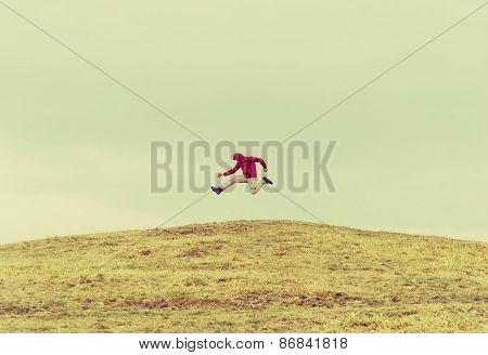 Happy Traveler Jumping On The Hill