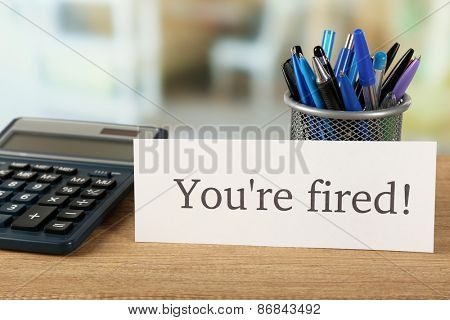 Message You're Fired on wooden table, on blurred background