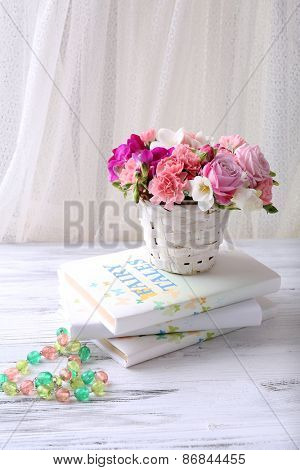 Beautiful fresh spring flowers with stack of books on curtain background
