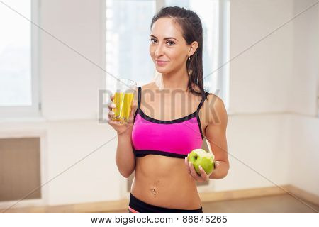 Gorgeous young athletic sportive woman in sport outfit holding fruit orange juice after the training