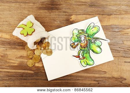 Greeting card for Saint Patrick's Day with Leprechaun and bag of coins on wooden table background