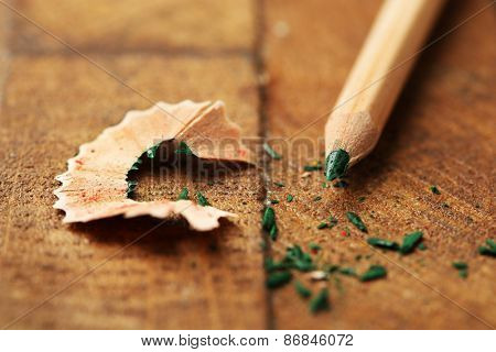 Wooden color pencil with sharpening shavings on wooden table