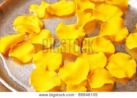 Rose petals in bowl on wooden background