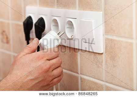 Hand Plugging Power Cord Into Wall Outlet