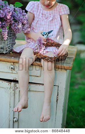 child girl with secateurs making lilac wreath in spring garden