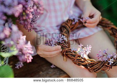 child girl making lilac wreath in spring garden