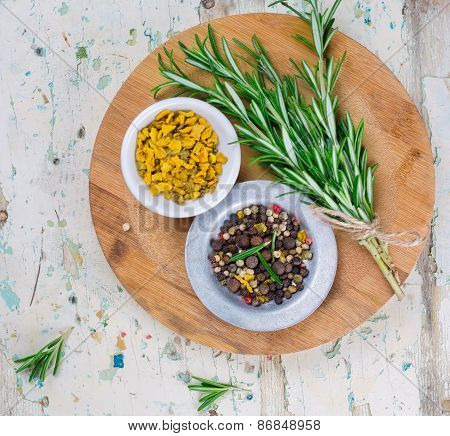 Spices, rosemary and pepper on wooden board