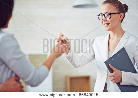 Young female broker giving her client key from new flat