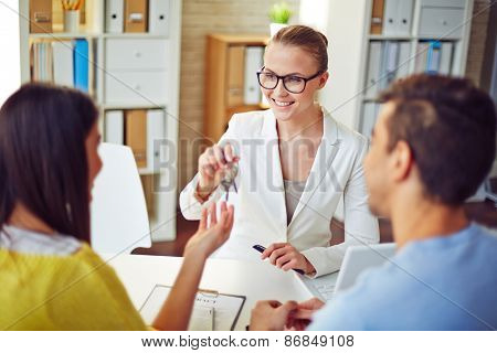 Female realtor giving young couple key from real estate