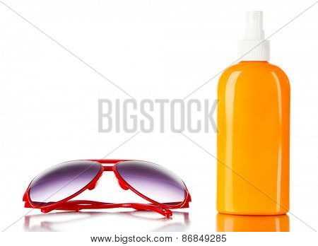Bottle of suntan cream with sunglasses isolated on white