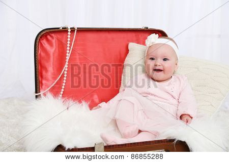 Cute baby girl sitting in big suitcase on carpet, on light background