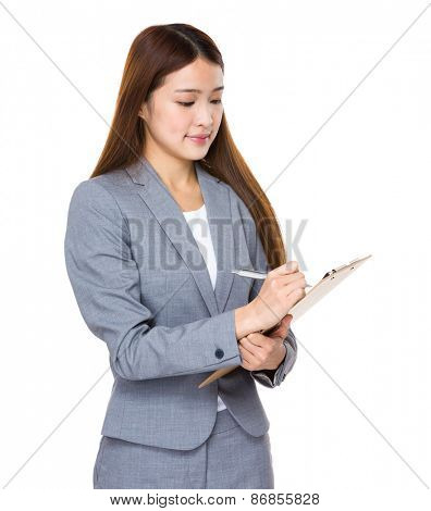 Asian businesswoman writing on clipboard
