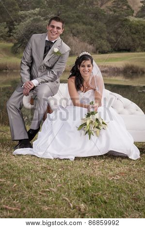 Happy newly wed couple sitting outdoors on couch