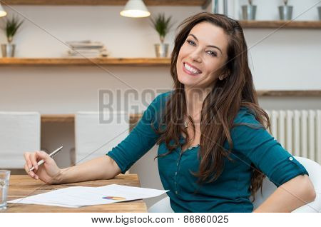 Portrait of smiling business woman sitting at desk with stockmarket document