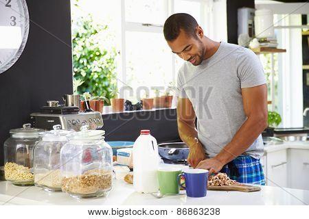 Young Man Wearing Pajamas Preparing Breakfast In Kitchen