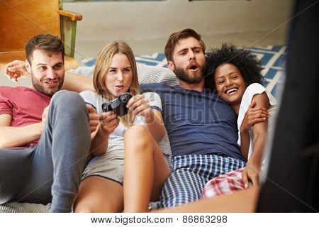 Group Of Friends Wearing Pajamas Playing Video Game Together