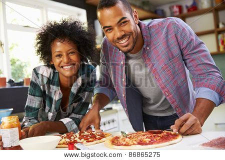 Young Couple Making Pizza In Kitchen Together