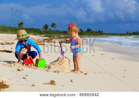 little boy and toddler girl playing with sand on the beach