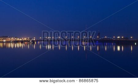 Night view of Riga bridge with reflection in Daugava river