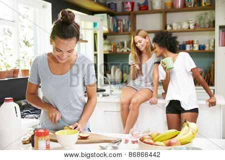Female Friends Making Breakfast Whilst Checking Mobile Phone