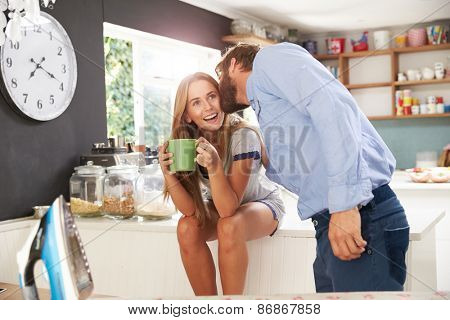 Man Getting Ready To Leave For Work Kisses Woman In Kitchen