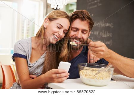 Young Couple Eating Breakfast Whilst Using Mobile Phones