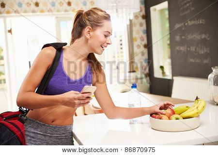 Woman Wearing Gym Clothing Choosing Fruit From Bowl