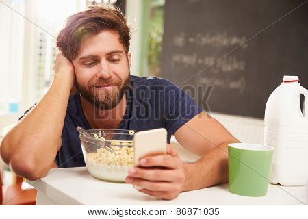 Young Man Eating Breakfast Whilst Using Mobile Phone