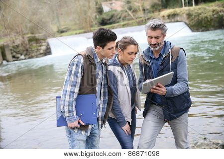 Porfessional with students in biology standing by river