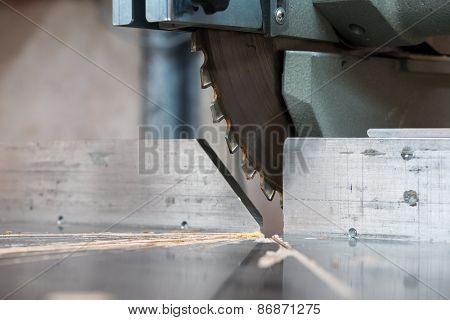 detail of fixed circular buzz miter saw blade and table