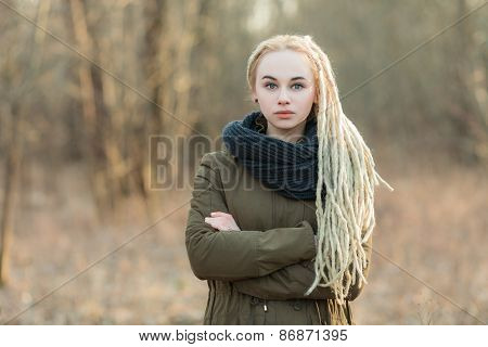 Young serious blonde hipster woman cold season outdoors