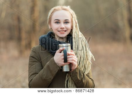 Young blonde woman with thermos cup cold season forest outdoors