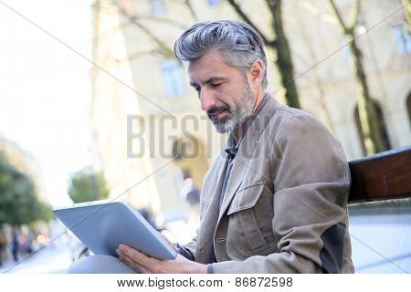 Mature man websurfing with tablet, sitting on public bench