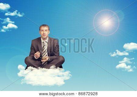 Businessman sitting in lotus position on cloud, holding golden lamp of Aladdin