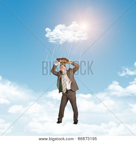 Businessman in suit standing on cloud and covered using briefcase from rain