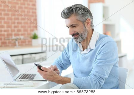 Trendy mature man using smartphone in front of laptop