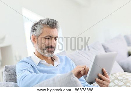 Mature handsome man websurfing on tablet at home