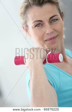 Portrait of mature fitness woman lifting dumbbells