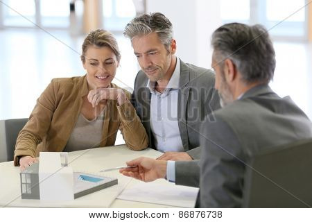 Mature couple meeting architect for construction project