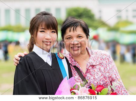 Mother is hugging her daughter for her master degree graduation
