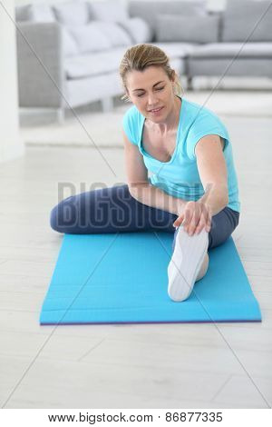 Middle-aged woman doing stretching exercises at home